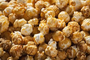 Golden caramel popcorn closeup. Background of popcorn. Snacks and food for a movie