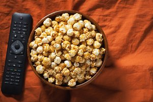 Wooden bowl with sweet popcorn and TV remote on orange bedding. Top view. Snacks and food for a movie