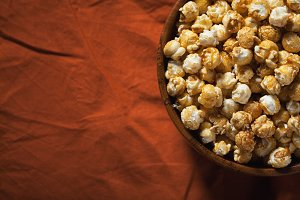 Wooden bowl with sweet popcorn on orange bedding. Snacks and food for a movie