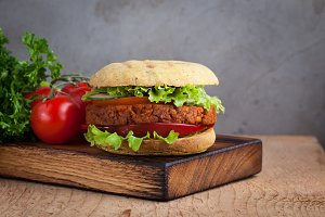 Fresh vegan Burger with tomato, cucumber, lettuce and vegan cutlet on wooden Board