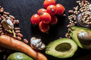 raw fresh vegan healthy fruit and vegetables on black dark surface