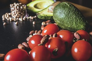 close up raw fresh fruits vegetables and nuts on dark surface