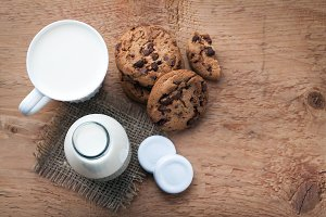 Two bottles of milk and chocolate chip cookies on dark background with copy space. Top view