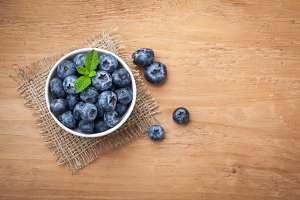 Blueberry on wooden table background. Ripe and juicy fresh picked blueberries closeup. Berries closeup top view with copy space