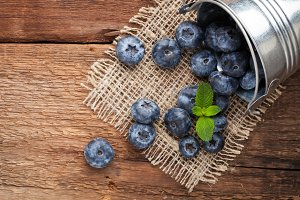 Blueberry on wooden table background. Ripe and juicy fresh picked blueberries closeup. Berries closeup with copy space
