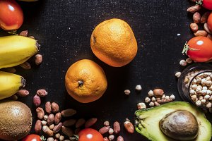 close up two mandarins on the black surface with seeds grains fruits and vegetables