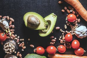 close up avocado with nuts and seeds with healthy vegetables and fruits on black dark surface
