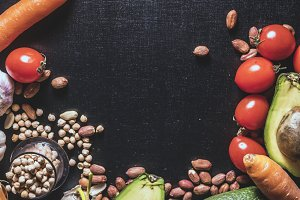 copy space on dark black surface with fresh vegetables seeds and nuts