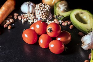 close up shot of raw vegan vegetables with tomato avocado seeds and nuts