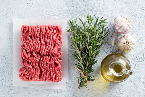 raw minced beef, rosemary, olive oil. top view