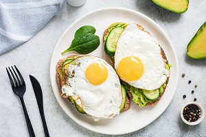 Two toasts with egg and avocado