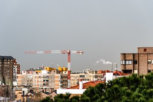 Cityscape with construction crane against gray sky