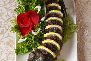Delicious stuffed carp with lemon. Gefilte fish with lettuce leaves.