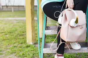 Women's legs in jeans and sneakers, backpack, headphones and smart phone