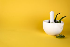 Aloe vera leaf, white mortar full of chopped aloe and bottles of aloe gel or infusion.