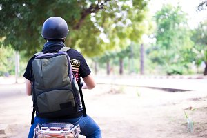 Back of Young happy and handsome male motorcyclist in helmet riding on motorbike on country road