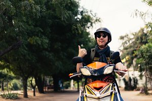 Young happy and handsome male motorcyclist riding on motorbike giving thumbs up and positive