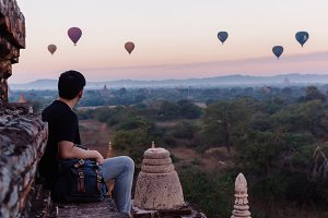 Silhouette of young male backpacker sitting and watching hot air balloon travel destinations in Bagan, Myanmar