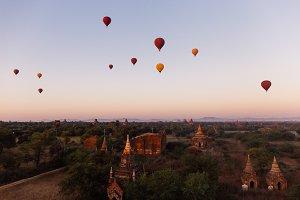Hot air balloons floating around Burmese pagoda heritage site during sunrise landscape
