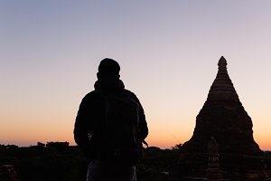 Silhouette of young travel man watching sunrise in temple pagoda area
