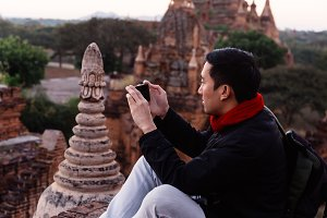 Young man taking a photo with mobile phone in temple stupa architecture scenery