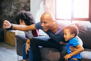 Happy African American family of three watching tv and cheering sport games on sofa at home