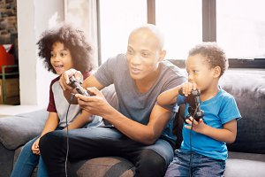African American family at home sitting in sofa couch and playing console video games together