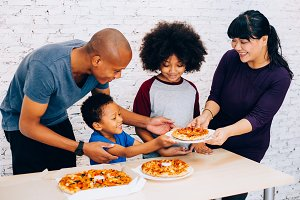 Happy family of African American parents and little boy and girl having pizza together happily at home. Family and parenthood concept
