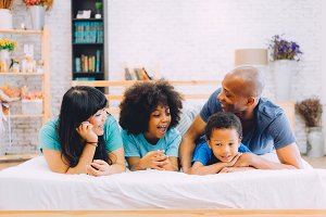 Happy African American family laying on bed at home, happily talking to each other. Parenthood and family concept