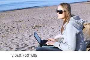 Woman in sunglasses using laptop