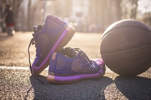 close up modern basketball shoes and ball on the outside court, sunshine day