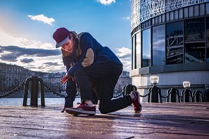 portrait of manin jacket and snapback dancing in the urban streets of the city