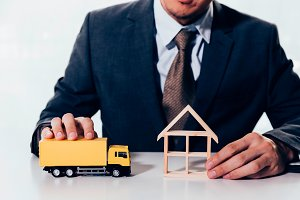 Businessman holding a miniature of house and delivery toy truck, indicating the concept of direct delivery to house, moving relocation and freight service