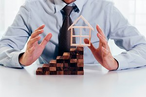 Close up of businessman using hand to protect residential house and real estate building. Concept of protecting, insuring, mortgage, loan, business finance and real estate
