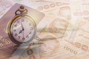 pocket watch over thai baht banknote