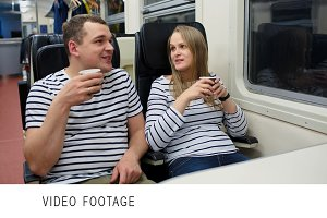 Man and woman drinking tea in train
