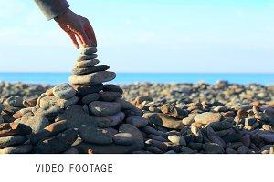 Hand putting last stone on pyramid