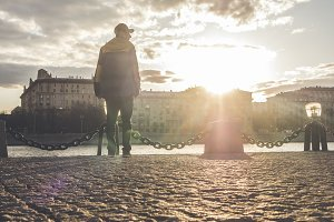 man in snapback standing in the city on a golden hour sunet near the river