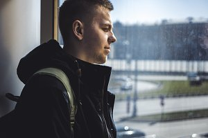 close up portrait of young man standing near the window looking in it