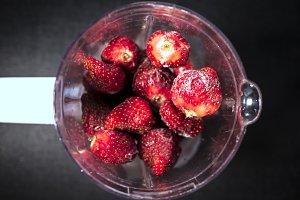 fresh iced juicy strawberries in blender top down view on dark surface