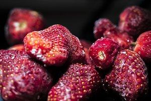 close up raw fresh frozen strawberries on black dark background