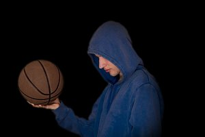 hooded street ball player with basketball in the dark