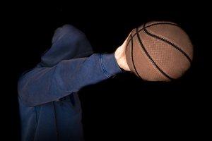 hand palming basketball close up in dark studio