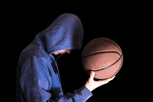 portrait man holding basketball in hands isolated dark