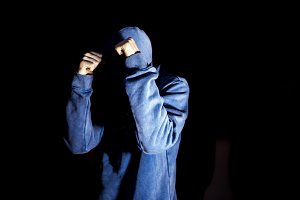 young man in the hood fighting in the dark blocking attack isolated black
