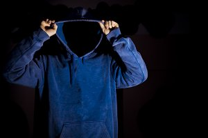 young man putting on hoodie hood on isolated black background