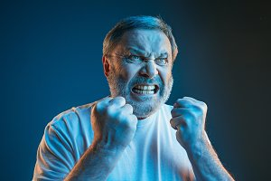 The senior emotional angry man screaming on blue studio background