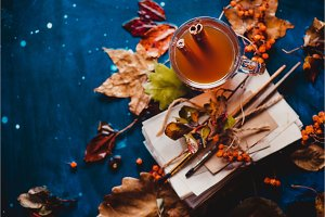 Autumn flat lay with fallen leaves and a stack of artist scetches with painting brushes. Rainy still life with a glass tea cup on a wet wooden background with copy space.