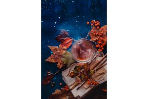 Steaming hot tea in a glass tea cup on a wet wooden background with copy space. Rainy autumn concept with fallen leaves