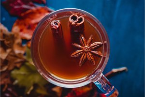 Tea cup with anise stars and cinnamon close-up. Out of focus autumn background with fallen leaves and berries. Rainy day concept with copy space.